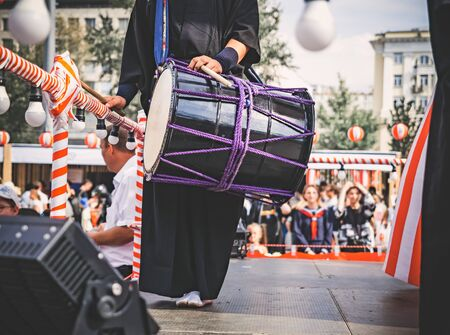 A male Japanese musician, a drummer standing on the stage Yagura is dressed in traditional Japanese black kimono and holds a taiko drum - ready to performance