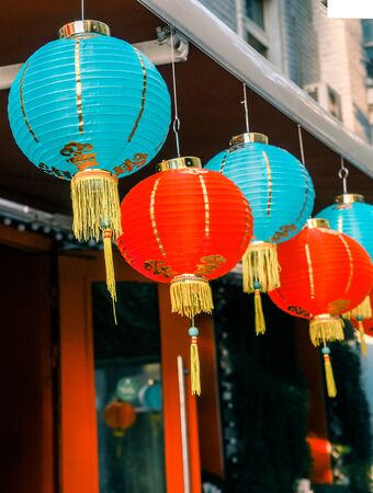 Chinese Paper Lanterns Sway on Wind on the Roof of a Building by Day on the Street