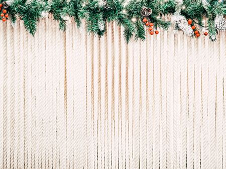 Christmas background for text. The rope stretched in rows is decorated with a hat made of Christmas tree ornaments decorated with cones and winter berries. 스톡 콘텐츠
