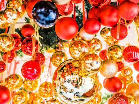 Many large golden balls with festooned fir tree garlands and red ribbons are hung indoors. New Year and Christmas tree decorations. Beautiful Christmas background. Street decorations in Europe