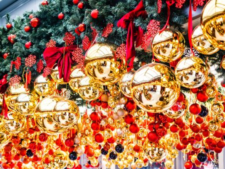 Many large golden balls with festooned fir tree garlands and red bows and snowflakes are hung. New Year and Christmas tree decorations. Beautiful Christmas background. Street decorations in Europe