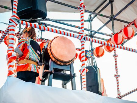 The stage of the Yagura with a drummer girl big japanese taiko drum Wadaiko. Paper red-white lanterns Chochin Scenery for the holiday Obon when people dance of Bon Odori