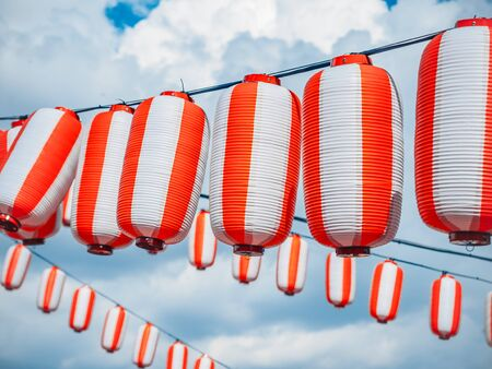 Paper red-white japanese lanterns Chochin hanging on cloudy blue sky background. Summer background 스톡 콘텐츠