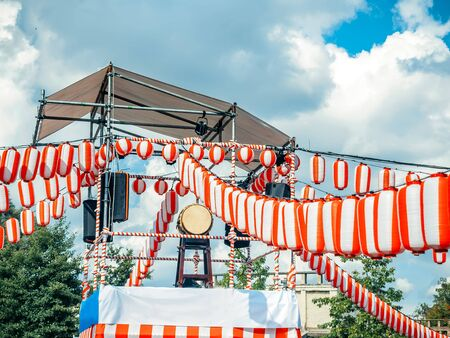 The stage of the Yagura with a big japanese taiko drum Odaiko. Paper red-white lanterns Chochin Scenery for the holiday Obon when people dance of Bon Odori