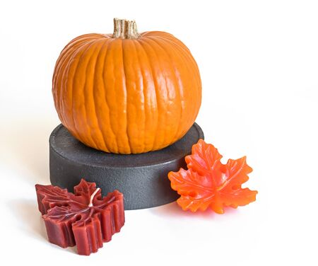 Small orange pumpkin on a gray stand and candle maple leaves isolated on white background 스톡 콘텐츠