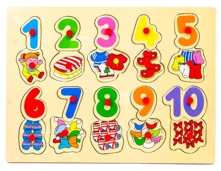 Wooden puzzle with numbers and arithmetic signs with pictures of items. Childrens hand takes the figures from the puzzle. Preschool educational game for the development of memory, logical thinking and 스톡 콘텐츠