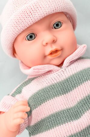 Cute baby doll for girl in knitted dress close up