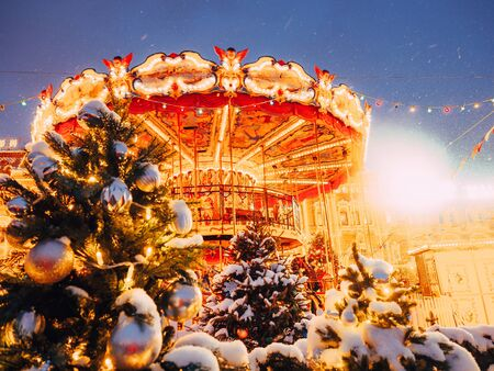 Beautiful brightly glowing carousel on the Red Square decorated and arranged for Christmas and New Year. Christmas fairy illuminated turnabout . Luminous roundabout rotates. Wonderful magic xmas background. Rotating merry go round in Moscow city