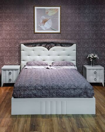 Bedroom interior. Cozy modern bed furniture with patterned bed with leather upholstery headboard . Soft brocade fabric bed. Classic modern furniture in home interior.