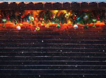 Christmas fir tree garland with christmas tree decoration on wooden house wall. Bright Christmas and New Year background with empty space for text