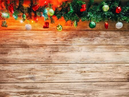 Christmas fir tree garland with christmas tree decoration on wooden board. Bright Christmas and New Year background with empty space for text