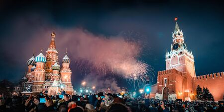 New Years Eve in Moscow. Fireworks on Red Square near the Spasskaya Tower on New Years Eve. Multicolored salute in the Kremlin. A large crowd of people celebrates the New Year on Red Square. Many unrecognizable people gathered for a universal celebration