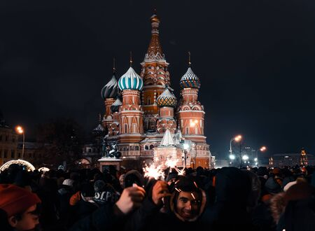 Moscow, Russia -January 1, 2019: Many people gathered for a universal celebration New Years in Moscow on Red Square near the St. Basils Cathedral. New Years Eve Outdoor. A large crowd of people celebrates on Red Square. People hold sparklers in their hand