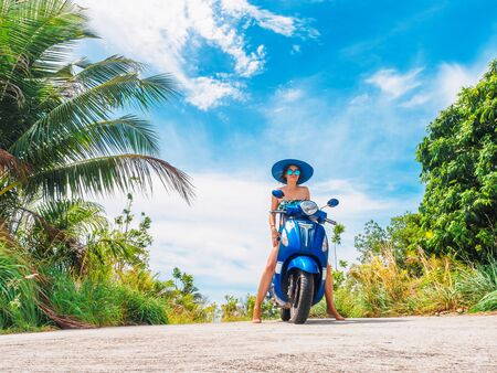 Crazy funny woman with flying hair riding a motorbike on a blue sky and green tropics background. Young girl with dark hair in sunglasses on a blue scooter in vintage style racing downhill. Concept of summer holidays and vacation adventures.