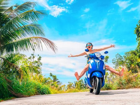 Crazy funny woman with flying hair riding a motorbike on a blue sky and green tropics background. Young bizarre girl with dark hair in sunglasses on a blue scooter in vintage style racing downhill. Concept of summer holidays and vacation adventures and wanderlust