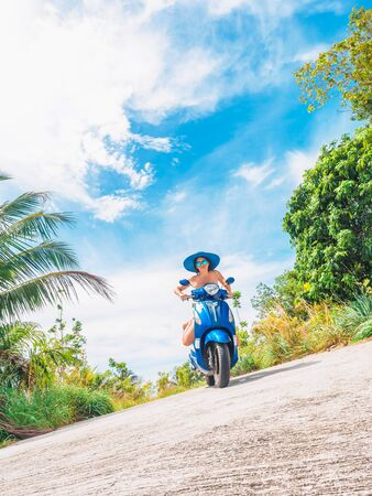 Crazy funny woman with flying hair riding a motorbike on a blue sky and green tropics background. Young bizarre girl with dark hair in sunglasses on a blue scooter in vintage style racing downhill. Concept of summer holidays and vacation adventures. Stockfoto