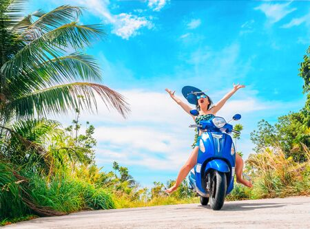 Crazy funny woman with flying hair riding a motorbike on a blue sky and green tropics background. Young girl with dark hair in sunglasses on a blue scooter in vintage style racing downhill. Concept of summer holidays and vacation adventures and wanderlust Stockfoto