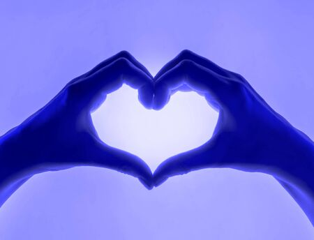 Hands in the form of heart blue shades background. heart symbol with hand. valentines day card. Womans hands silhouette in form of heart.