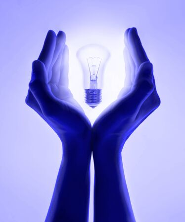 Female hands and holding luminous light bulb. Electric incandescent light bulb in hand on purple background. Inspiration Ideas concept