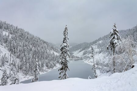 Amut Lake - Alpine landslide lake located in the Solnechny District of the Khabarovsk Kray, Russia . Beautiful taiga hills on Far East of Russia in early october. Taiga in winter. Beautiful nature. Frosty and gloomy weather