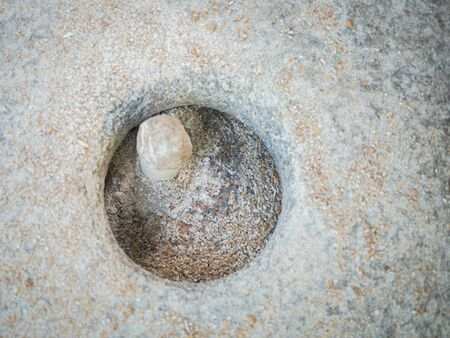 Rotary discoid mill stone for hand-grinding a grain into flour. Medieval hand-driven millstone grinding wheat. The ancient Quern stone hand mill with grain close up.
