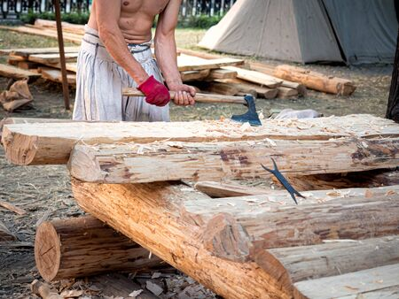 Carpenter bare-chested in medieval cotton clothes working with hardwood with an ax. A man manually cuts a wooden board with an ax. Construction site. Ax cut a log closeup. Slivers fly in different directions. Construction of a wooden house. Construction site. The construction of the old traditional russian house izba Reklamní fotografie
