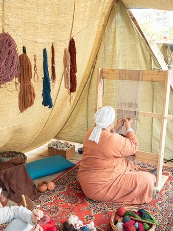 Times and Epochs Festival. Female Weaver Weaves a Canvas With a Pattern of Wool Yarn. Woman Weaves Using a Traditional Wooden Loom.