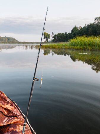 Fishing on the inflatable boat on the river. Inflatable kayak with rod with spoon n the summer day on the river. Leisure on water. Activities outdoor. Fishing from a boat. Handheld shot oning boat. Reklamní fotografie
