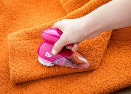 Clothes care. Lint shaver or fabric shaver or fuzz remover in female hand. Woman removing lint on orange wool coat with handheld electric defuzzer. Фото со стока