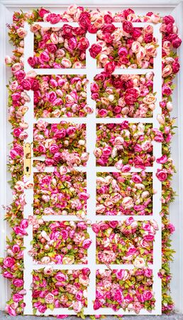 Creative collage Door in summer. Beautiful background of artificial pink peonies with white classic door. Floral rose background. Pink flowers background Фото со стока