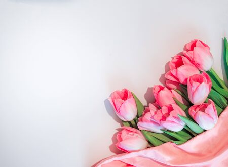 Pink flowers white background. Bouquet flowers rose tulips in the lower right corner on an isolated white background. Flat lay mock up, top view Фото со стока