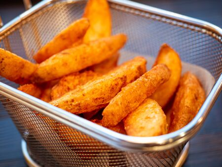 Deep-fried potato wedges. Basket of freshly made French fries close up.
