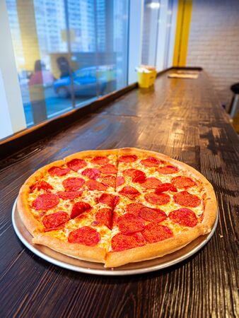 Just cooked Pizza pepperoni on a table in a cafe in front of a window with a panorama of the city. Appetizing hot pizza with slices of smoked sausage.