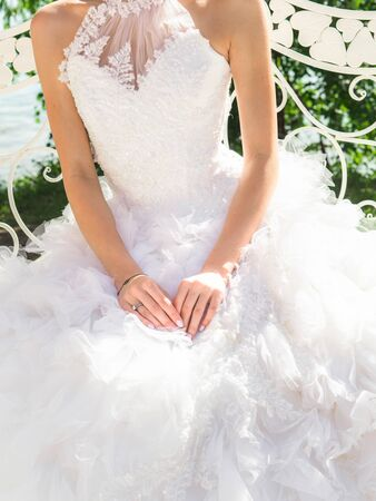Beautiful bride in white wedding dress sits on a swing with her hands on fluffy skirt a sunny day.
