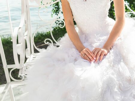Beautiful bride in white wedding dress sits on a swing with her hands on fluffy skirt a sunny day