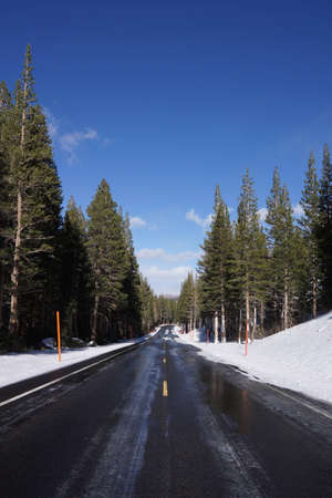 Wet road in mountain with snow in winter