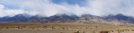 Panorama image of mountain landscape with fog and snow