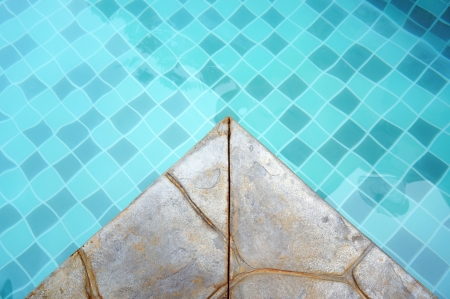 Turquoise mosaic tile in a swimming pool with stone edge