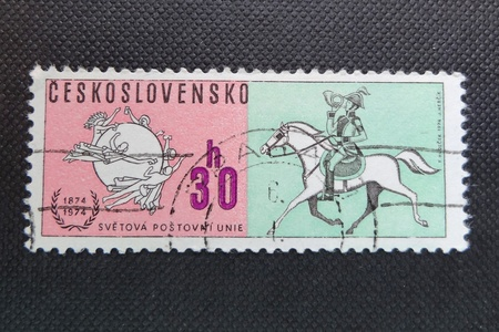 posthorn: CZECHOSLOVAKIA - CIRCA 1974: A stamp printed in former CZECHOSLOVAKIA commemorates centenary of Universal Postal Union. It shows emblem of the Union and a horseman with posthorn, circa 1974