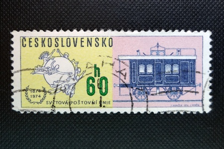 CZECHOSLOVAKIA - CIRCA 1974: A stamp printed in former CZECHOSLOVAKIA commemorates centenary of Universal Postal Union. It shows emblem of the Union and a railway carriage, circa 1974