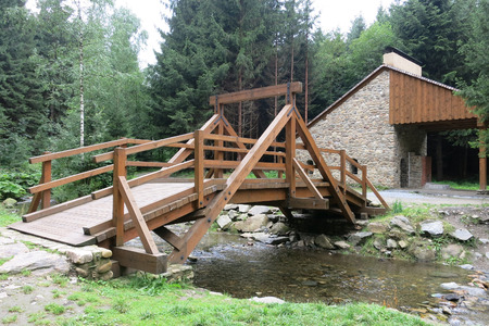 replica: Zlate Hory, Czech republic - August 1 2016: Replicas of wooden bridge and gold ore melting furnace in an open-air museum in Zlate Hory, Czech Republic.