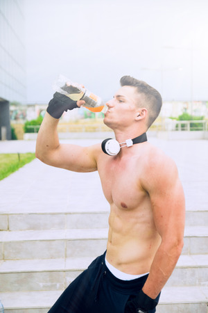 energizing: Young proud man drinks energizing water after very hard training in front of sport center Stock Photo