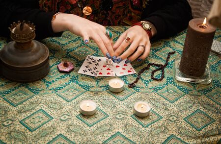 Gypsy fortune-teller laid out the cards on the table next to candles, bahur and other magical paraphernalia
