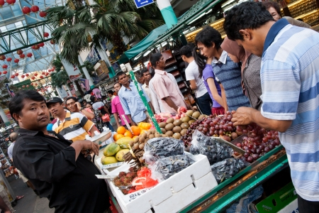 KUALA LUMPUR, MALAYSIA - AUGUST 30  Merchant sells fruit on busy street market in Kuala Lumpur s famous Chinatown district located around Jalan Sultan on August 30, 2011 in Kuala Lumpur