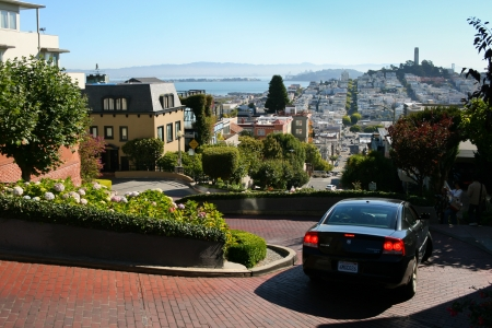 telegraph hill: SAN FRANCISCO - SEPTEMBER 24  Dodge negotiates narrow and twisty Lombard street while tourists take pictures of this famous place on September 24, 2010 in San Francisco  Telegraph Hill can be seen in the background