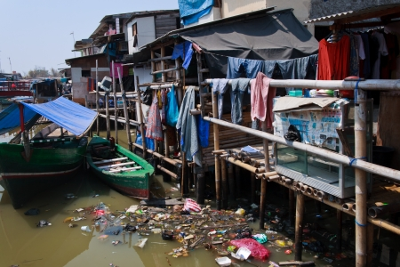 slum: JAKARTA, INDONESIA - SEPTEMBER 6: Slum located not far from business heart of the city on September 6, 2011 in Jakarta. People live in various bamboo or wooden huts build on a river full of garbage.