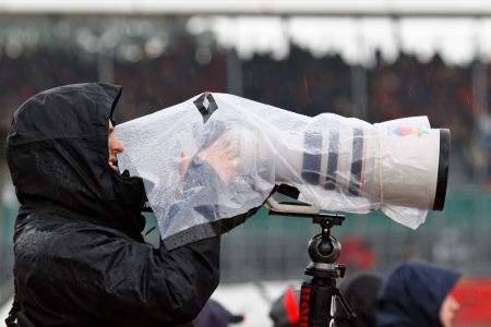 telezoom: SILVERSTONE, UK - JULY 6: Photographer takes shots in heavy rain during practice session of F1 British GP on July 6, 2012 in Silverstone. Difficult weather conditions are typical for this race.