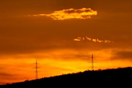 over the hill: La salida del sol de oro sobre colina con postes de electricidad