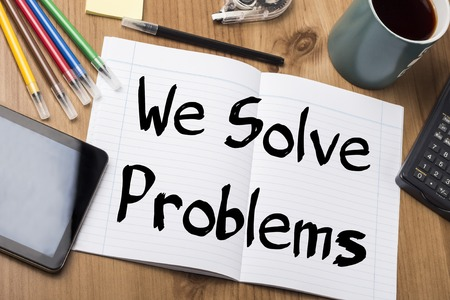 solve problems: We Solve Problems - Note Pad With Text On Wooden Table - with office  tools Stock Photo