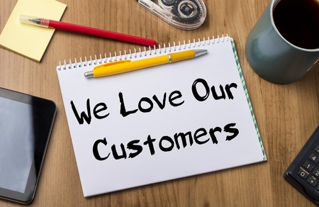 We Love Our Customers - Note Pad With Text On Wooden Table - with office  tools Stock Photo